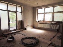 Стальной радиатор установлен под окном, а внутрипольный конвектор — перед балконной дверью